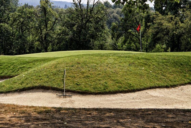 Monte da grama do campo de jogos do golfe com a bandeira no furo e no ancinho fotos de stock royalty free