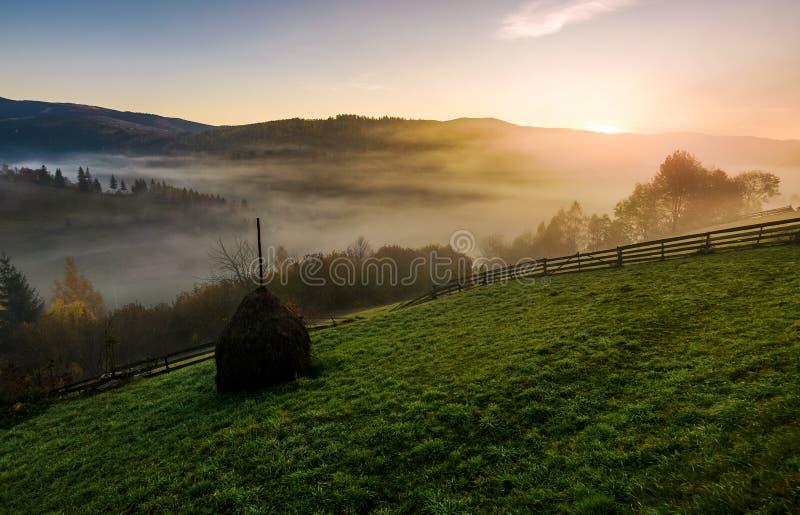Monte de feno na manhã nevoenta do outono nas montanhas fotografia de stock