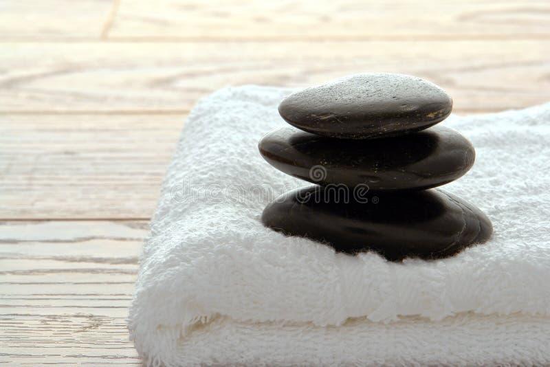 Monte de pedras de pedra lustrado quente preto em uma toalha em uns termas foto de stock royalty free