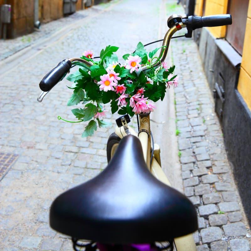 Monte en bicicleta con el manojo de flores en barra de la manija fotografía de archivo libre de regalías