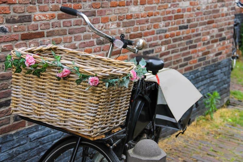 Monte en bicicleta con la cesta de mimbre adornada flor cerca de la pared de ladrillo foto de archivo