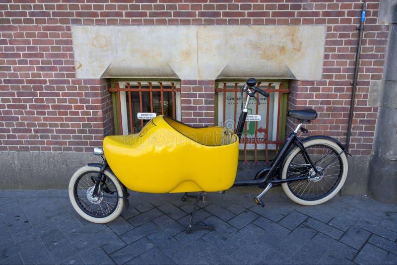 Monte en bicicleta con un cochecito de bebé bajo la forma de zapatos Klomp del holandés fotografía de archivo