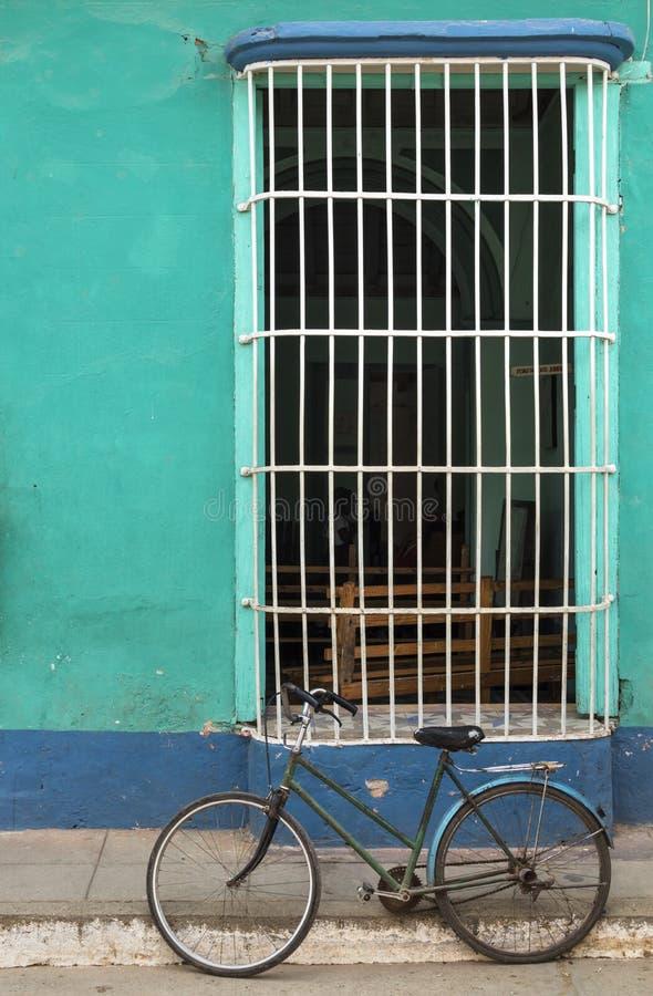 Monte en bicicleta delante de una casa colonial en Trinidad, Cuba foto de archivo libre de regalías