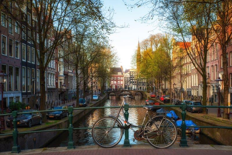 Monte en bicicleta en el puente con las casas tradicionales holandesas y el canal de Amsterdam en Amsterdam, Pa?ses Bajos fotos de archivo