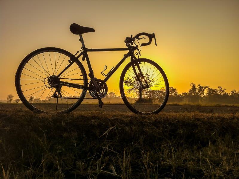 Monte en bicicleta en imagen rural del paisaje de la paja con mañana de la silueta foto de archivo