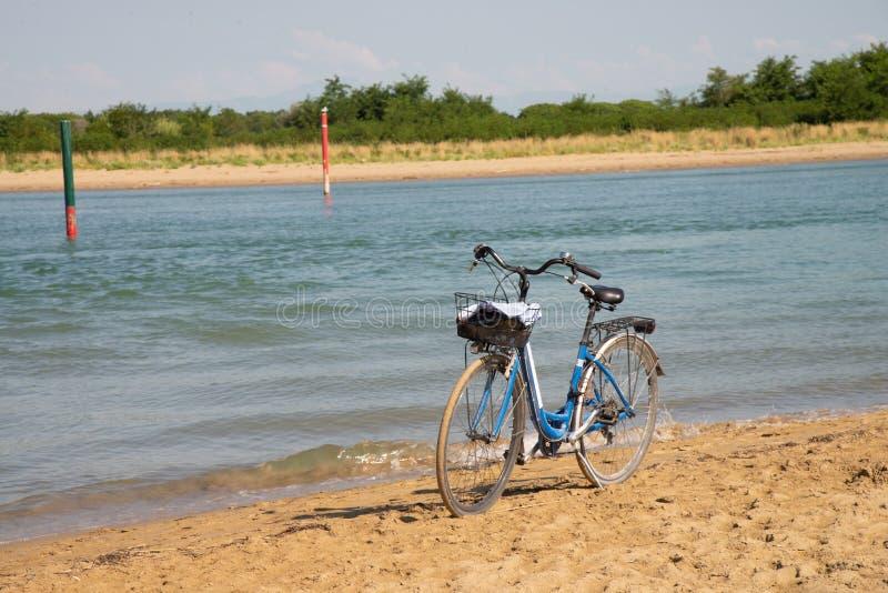 Monte en bicicleta en la orilla arenosa en la boca del río Livenza, Bibione, Véneto, Italia imagenes de archivo
