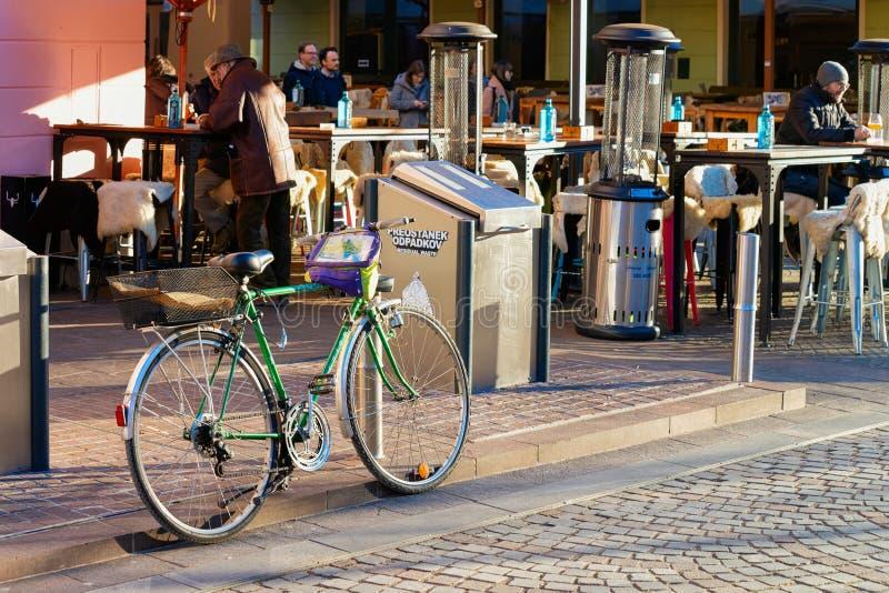 Monte en bicicleta parqueado y gente que bebe en café de la calle en Ljubljana imágenes de archivo libres de regalías