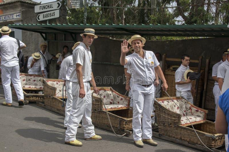 Monte, Funchal/MADÈRE - 22 avril 2017 : Hommes avec l'uniforme blanc traditionnel, canotiers de paille et avec des voitures de pa image libre de droits