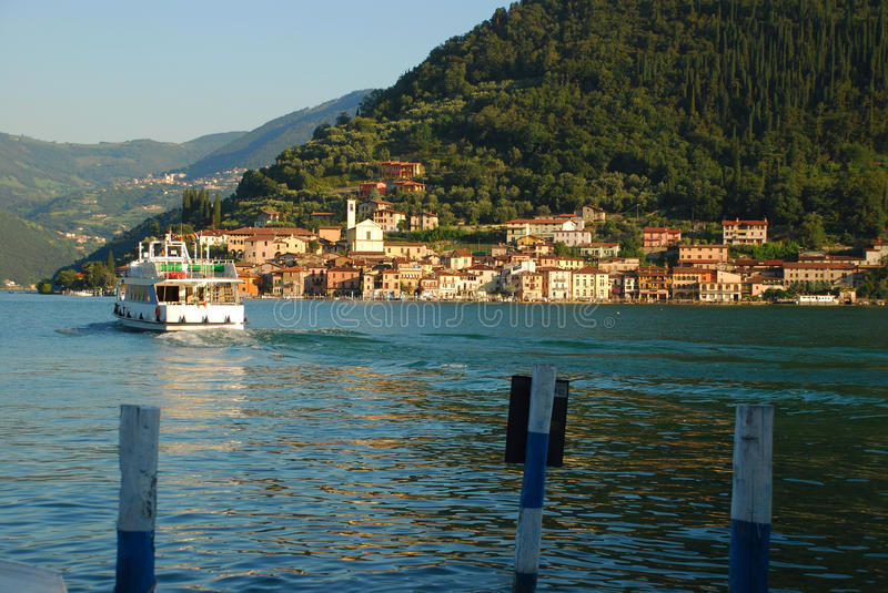 Lake Iseo, Monte Isola ferry, Italy. The village of Peschiera Maraglio on Montisola island and approaching boat, lake (lago) Iseo , Italy stock images