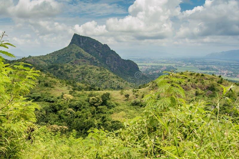 Monte, montanha, e floresta verde sob o céu nebuloso e vila na distância fotografia de stock