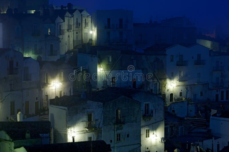 Monte Sant`Angelo town in Foggia, Gargano peninsula in Italy. Night scene with old buildings with lights. Travel in Europe, magi. C evening royalty free stock images