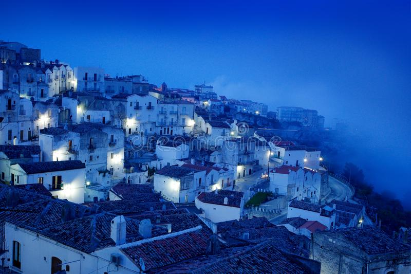 Monte Sant`Angelo town in Foggia, Gargano peninsula in Italy. Night scene with old buildings with lights. Travel in Europe, magi. C evening royalty free stock image