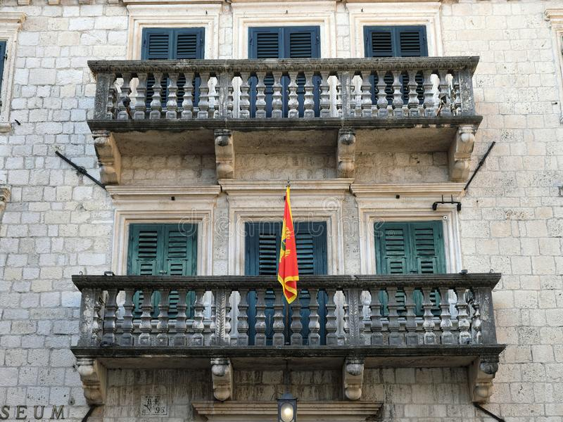 Montenegrin Flag Flying From Balcony, Kotor, Montenegro. Colourful Montenegrin flag flying from the balcony of an historic building with green wooden window and stock images