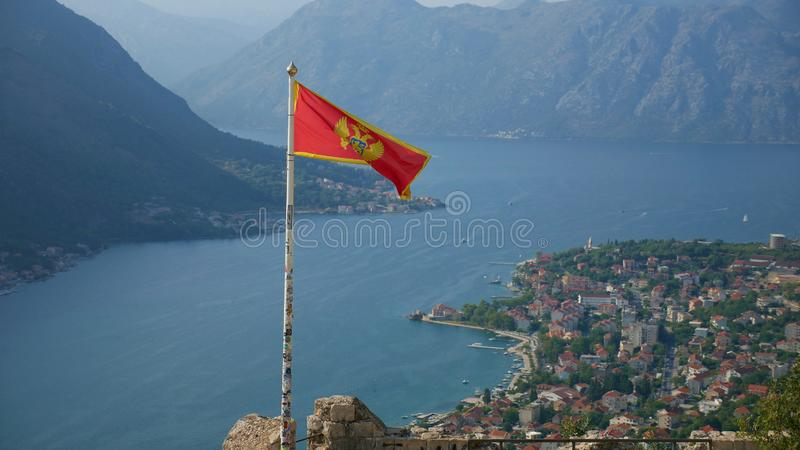 Montenegrin flag over Boka Kotorska. Picturesque bay and the his. Toric city of Kotor inscribed on the UNESCO list royalty free stock photo