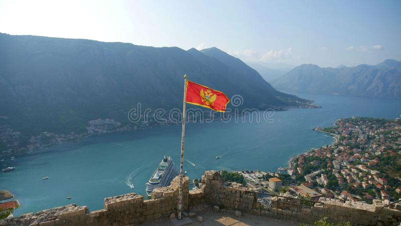 Montenegrin flag over Boka Kotorska. Picturesque bay and the his. Toric city of Kotor inscribed on the UNESCO list royalty free stock image