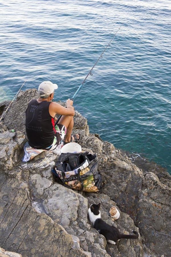 Montenegro, Budva - 14 de julio de 2018: La pesca del pescador en el mar en la orilla de piedra, y el gato está esperando la capt imagen de archivo libre de regalías