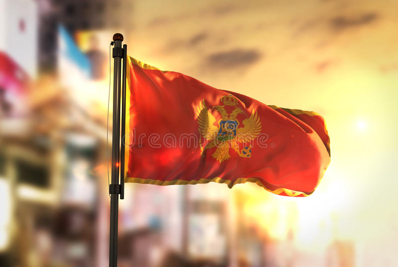 Montenegro Flag Against City Blurred Background At Sunrise Backlight. Sky royalty free stock photography