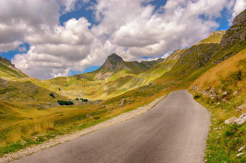 Montenegro, national park Durmitor, road,mountains and clouds. Daytime sunlight landscape. Montenegro, national park Durmitor, road,mountains and clouds royalty free stock photos