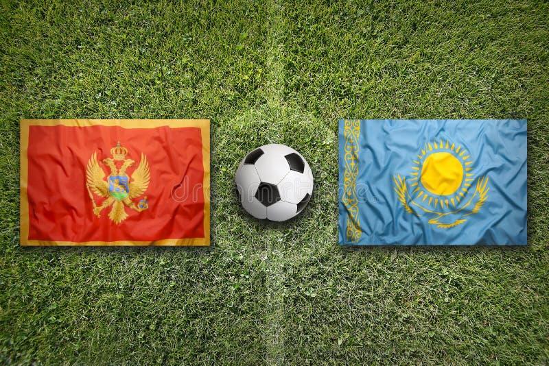 Montenegro versus De vlaggen van Kazachstan op voetbalgebied royalty-vrije stock fotografie