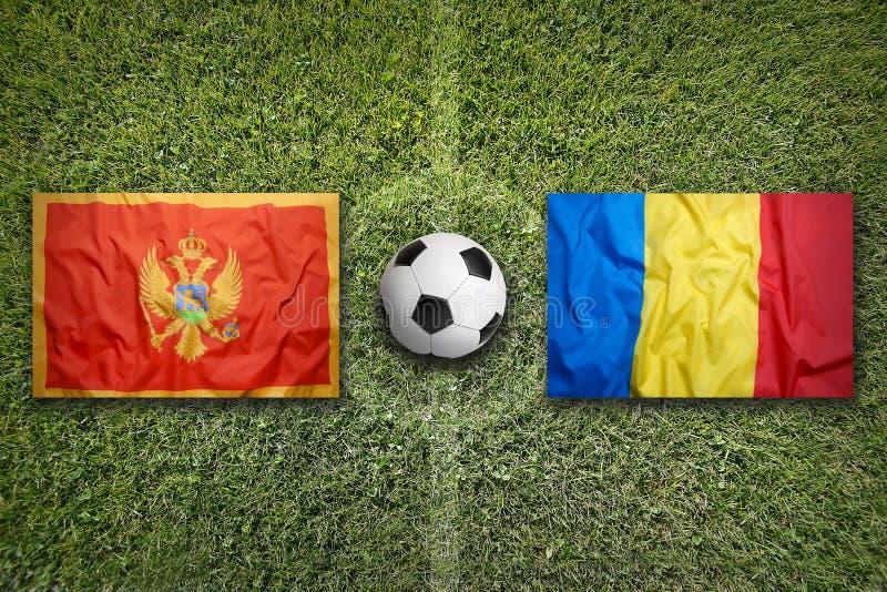 Montenegro versus De vlaggen van Roemenië op voetbalgebied stock afbeeldingen