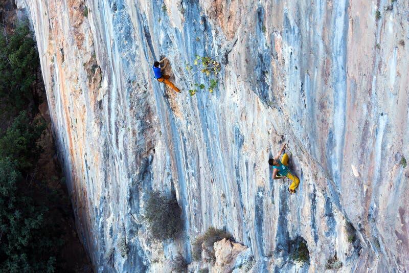 Monter de mur rocheux de couleur peu commune élevée et de deux grimpeurs photographie stock libre de droits