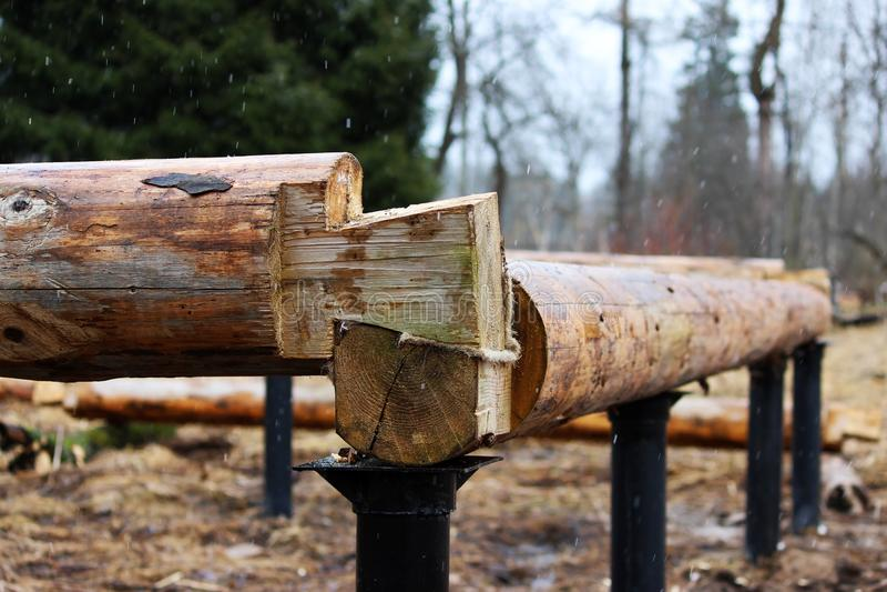 Montera en träram och byggande av ett hus Ryssland Textur av gamla träjournaler och den columnar grunden för metall royaltyfri fotografi
