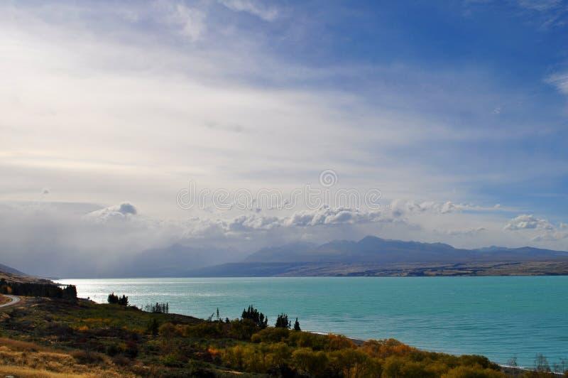 Montera kocksynvinkeln med sjön Pukaki och vägen som leder till monteringskockbyn arkivbilder