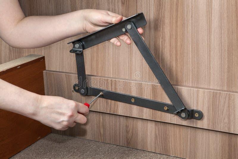 Monterande möblemang, skruvade händer lyfter upp justerbar metall för säng fotografering för bildbyråer