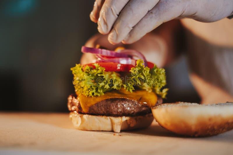 Monterande ostburgare för kökkock, genom att tillfoga löken royaltyfria foton