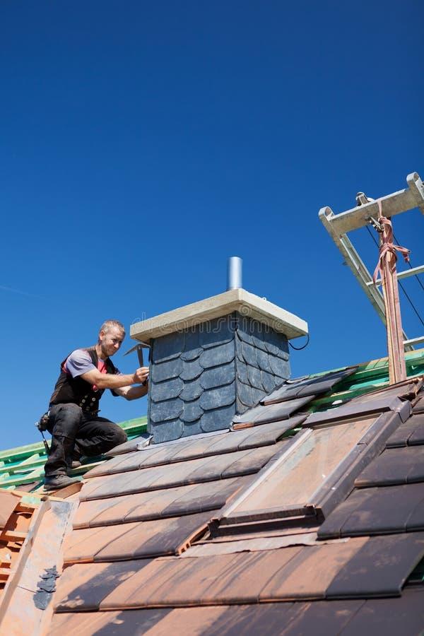 Monterande tegelplattor för Roofer på en lampglas arkivfoto