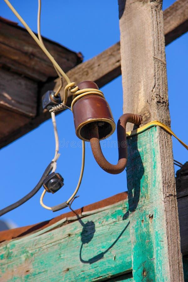 Monterat på en träplanka en omodern keramisk isolator för engjord elektrisk linje royaltyfri foto