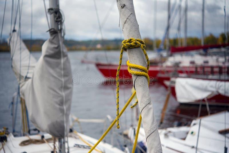 monterend wond een zeil van een staysail, op een vastgelegd jacht op de kust stock afbeeldingen