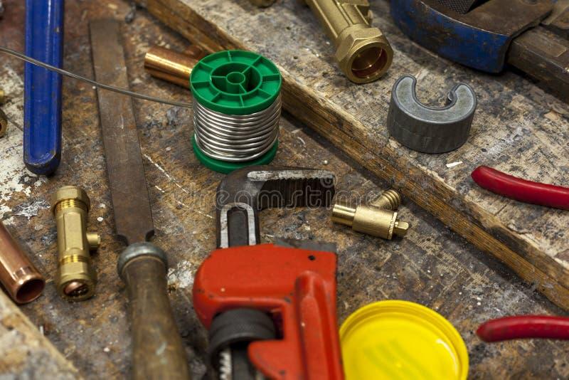 Monteringar för justerbar skiftnyckel och rörmokeripå en arbetsbänk royaltyfri foto
