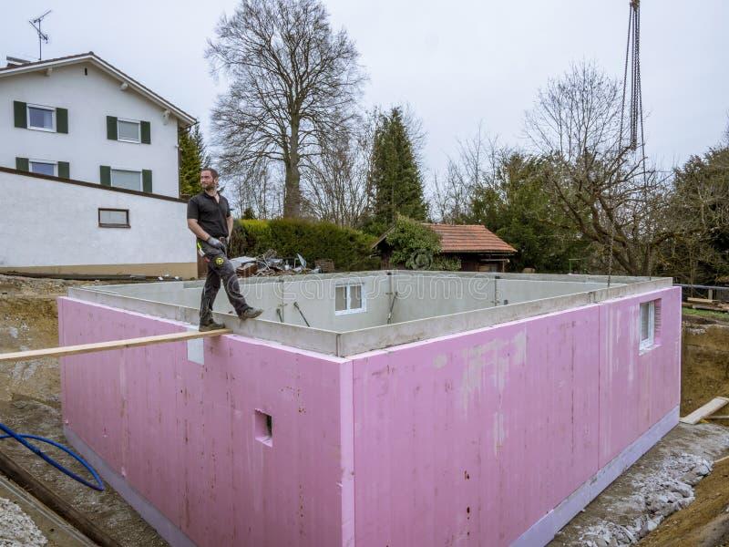Monteringshus arbetare i inställning - upp källareväggarna royaltyfria bilder