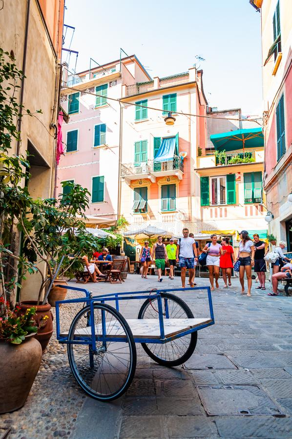 Blue cart with two wheels standing on a cozy street full of vibrant buildings, walking people, shops and bars in Monterosso Al. Monterosso Al Mare, Italy royalty free stock image