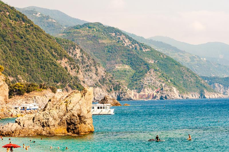 People swimming in the sea, yachts and boats traveling near the rocky coastline with green mountains on the background in royalty free stock photo