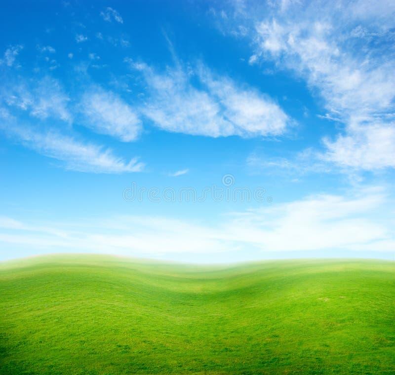 Montes da grama verde sob o céu azul. fotografia de stock royalty free