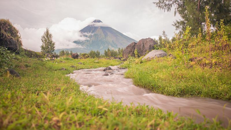 Montes do vulcão de Mayon com os rios de fluxo da montanha perto da cidade de Legazpi em Filipinas O vulcão de Mayon é um active fotos de stock