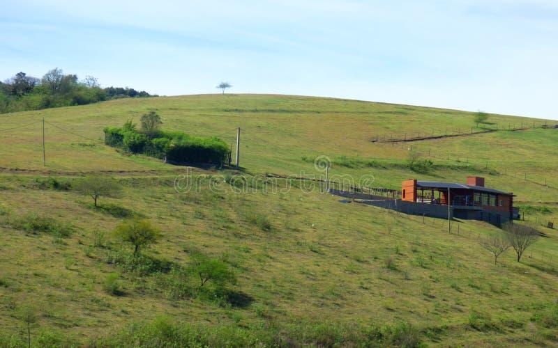 Montes e uma casa alaranjada imagem de stock