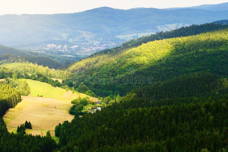 Montes e vale ensolarado nas montanhas de pedra Panorama vasto da paisagem pitoresca do campo em Sudetes, Polônia Silhueta do hom fotografia de stock