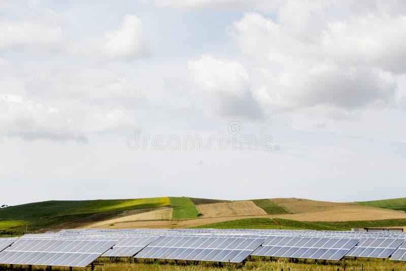 Montes e vinhedos com um campo dos painéis solares foto de stock royalty free