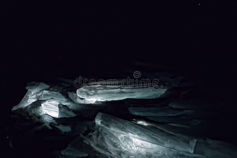 Montes luminosos do gelo azul do Lago Baikal na obscuridade fotos de stock royalty free