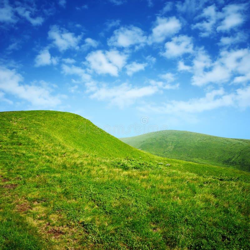 Montes verdes e céu azul com nuvens fotografia de stock royalty free
