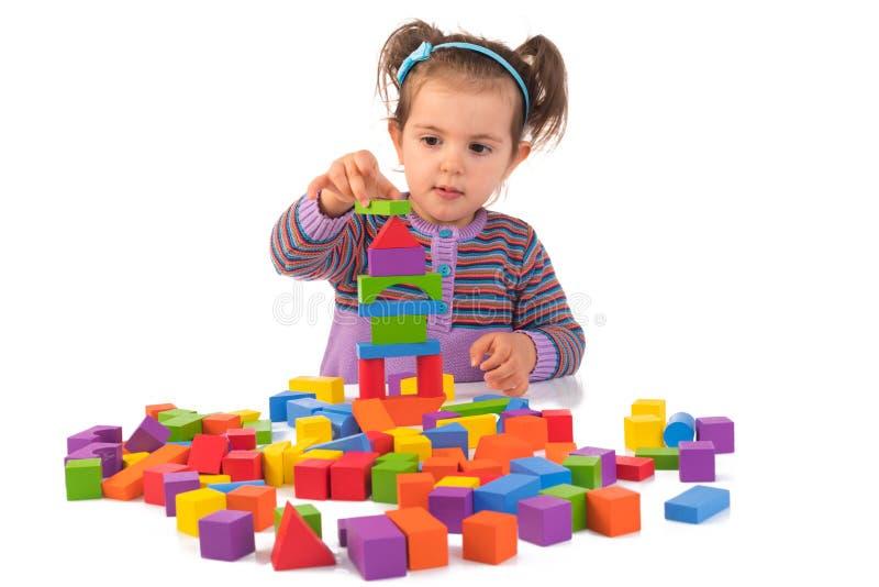 Montessori begrepp med den gulliga flickan som spelar isolerade träkuber royaltyfria foton