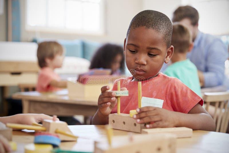 Montessori-Schüler, der am Schreibtisch mit hölzernen Formen arbeitet stockbild