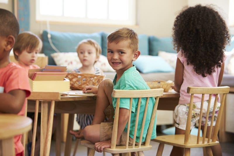Montessorileerling die bij Bureau met Houten Vormen werken stock afbeeldingen