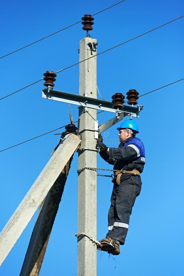 Monteur de lignes d'électricien de pouvoir au travail sur le pôle image stock