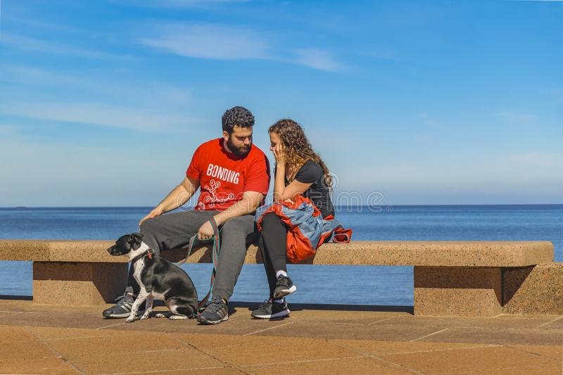 Couple with Pet at Boardwalk. MONTEVIDEO, URUGUAY, AUGUST - 2017 - Young couple with pet sitting at boardwalk at Montevideo city, Uruguay royalty free stock photo