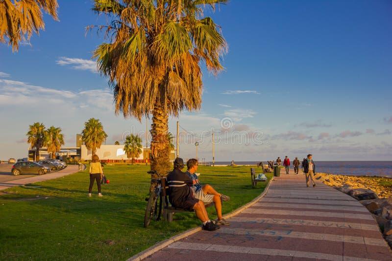 MONTEVIDEO URUGUAY - MAJ 04, 2016: trevlig solnedgång på becahen, några personer som tycker om solljuset och en trevlig blå himme royaltyfri bild