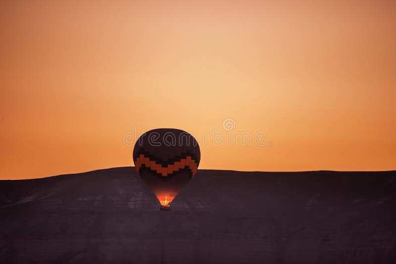 Montez en ballon en vol contre le contexte de la montagne à l'aube image stock